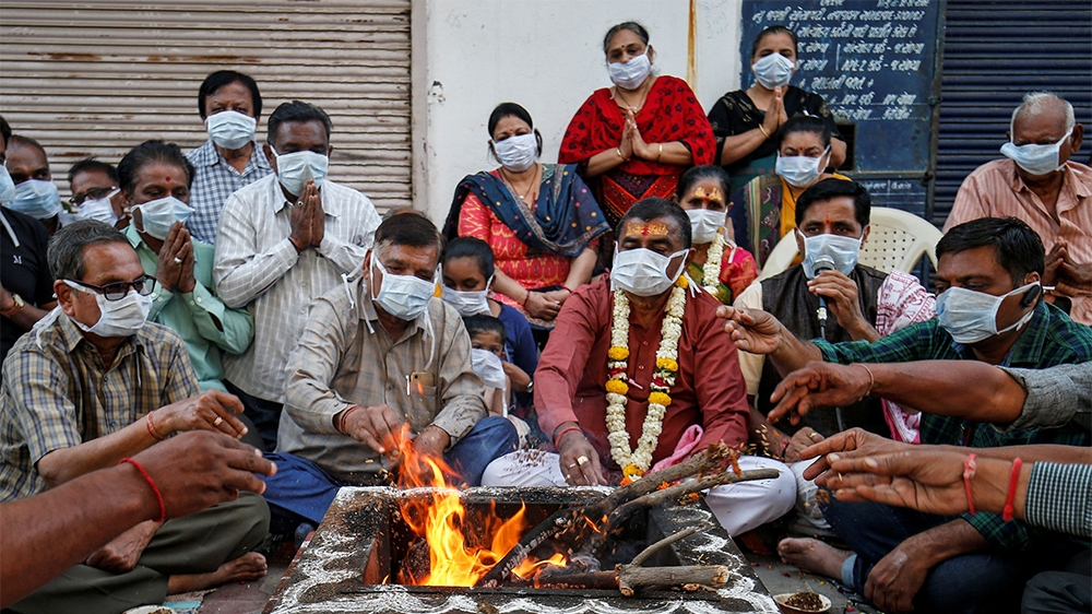 Hindu residents wearing protective masks perform prayers for the protection against coronavirus disease (COVID-19), outside a temple, in Ahmedabad, India, March 13, 2020. REUTERS/Amit Dave