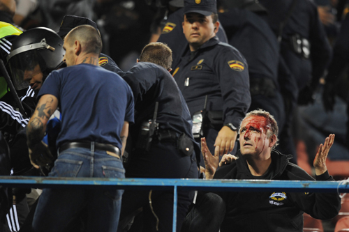 A bloodied Marseilles fan appeals to riot police as trouble sparks at Atletico's Vicente Calderon stadium [AFP]