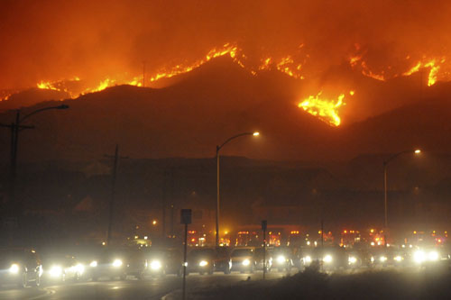 Two huge wildfires, fuelled by Santa Ana winds blowing at almost 100kph, have forced frantic evacuations in the US state of California [Reuter]