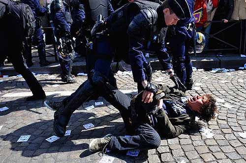 PARIS - APRIL 07:  French Police officer arrests a Pro Tibet demonstrator in front of the Eiffel Tower as the Olympic Torch Relay pass by on April 7, 2008 in Paris, France.  Pro Tibet protests have continued at Olympic torch relay in Paris, following 37 arrests that disrupted London?s torch relay on Sunday  (Photo by Pascal Le Segretain/Getty Images)