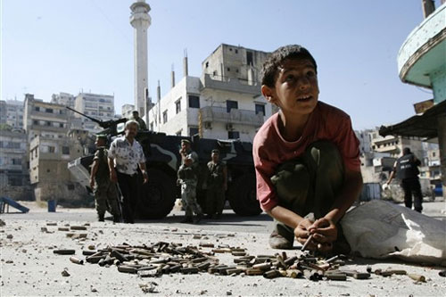 A Lebanese boy collects spent bullet casings from the street as soldiers secure the Bab al-Tebbaneh district of the northern city of Tripoli after four people were killed in gunbattles [AFP]