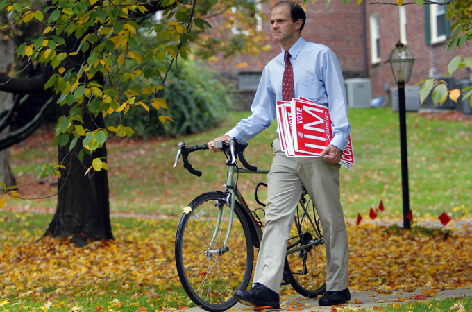 Jim Schneller, a self-avowed Tea Party activist, walks near his campaign headquarters with his bicycle and campaign signs in Wayne, Pennsylvania, on October 27, 2010. Schneller is not the type of congressional candidate a liberal Democrat would ordinarily support. Yet Schneller might not have become a candidate in Pennsylvania(***)s seventh congressional district were it not for his opponents [REUTERS]