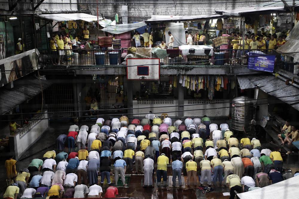 Muslim Filipino inmates pray during a downpour as they mar Eid al-Adha