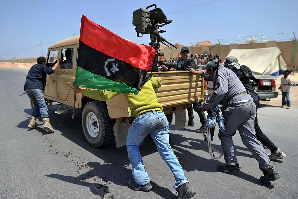 Libyan rebels push a seized government army vehicle past a migrant camp in Misurata [AFP]