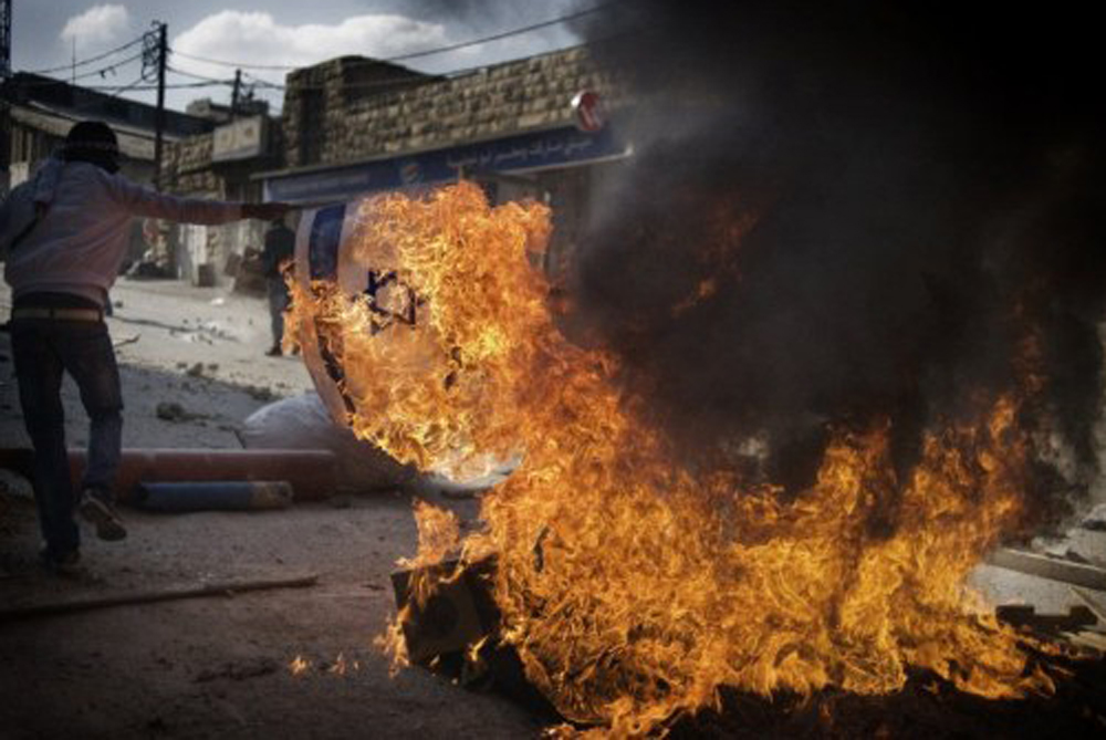"Masked Palestinian demonstrators in East Jerusalem(***)s Shuafat refugee camp burn an Israeli flag on Friday to mourn the ""Nakba"" or ""catastrophe"" - a reference to Israel(***)s establishment in 1948. [AFP]"