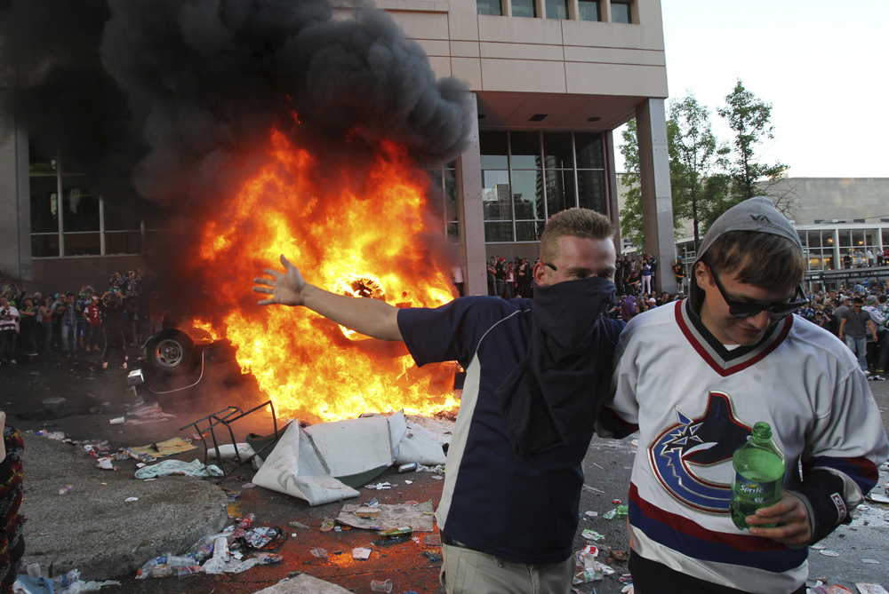 Vancouver Canucks fans overturn and set fire to a pickup truck after their team lose the Stanley Cup series to the Boston Bruins on Wednesday [Reuters]