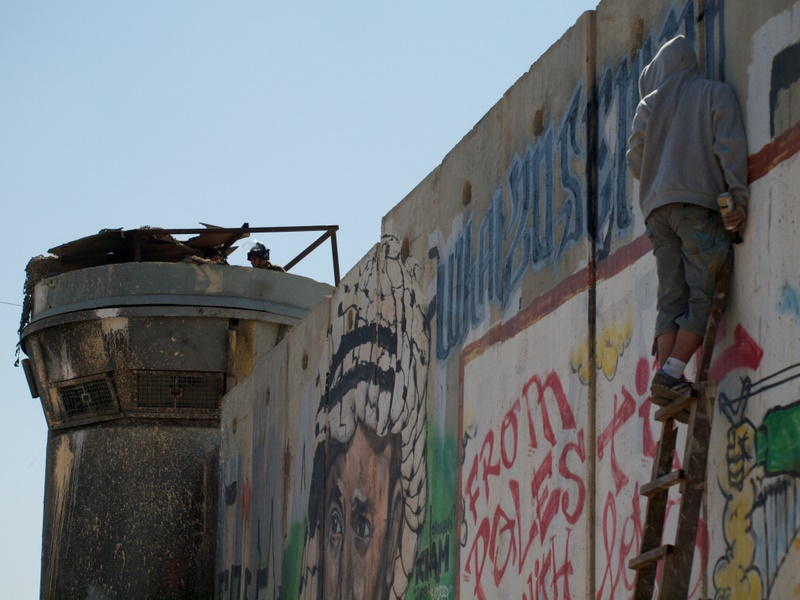 "A protester paints on the separation barrier while an Israeli soldier watches. He wrote the message: ""What will 20 September Change?"" - referring to the United Nations vote [Gregg Carlstrom/Al Jazeera]"