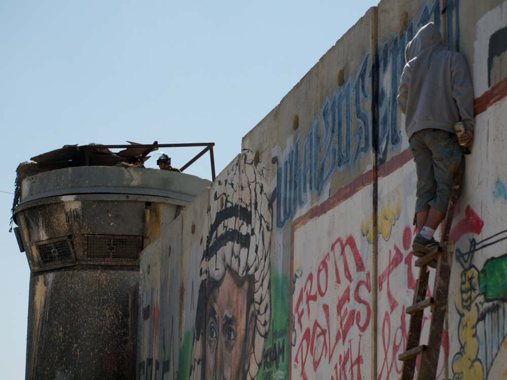 "A Palestinian man spray-paints graffiti on Israel(***)s separation barrier: ""What will September 20 change?"""