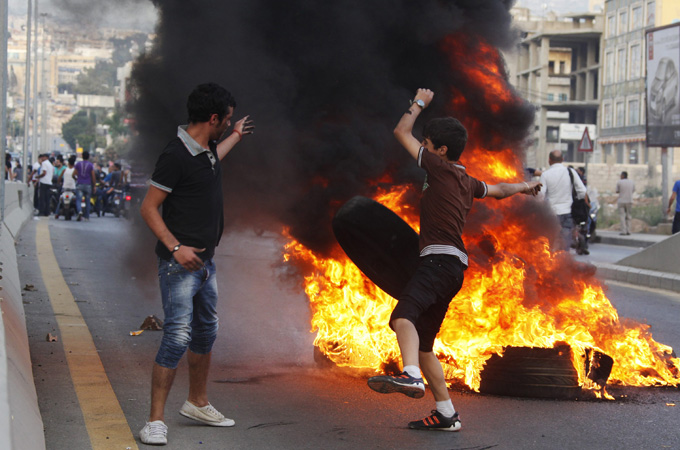 Lebanese men blocked a street in Beirut to protest the kidnapping of Lebanese Shias in Syria