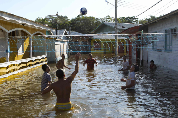 b59933d0a91 Residents play water volleyball a street flooded by the Rio Solimoes