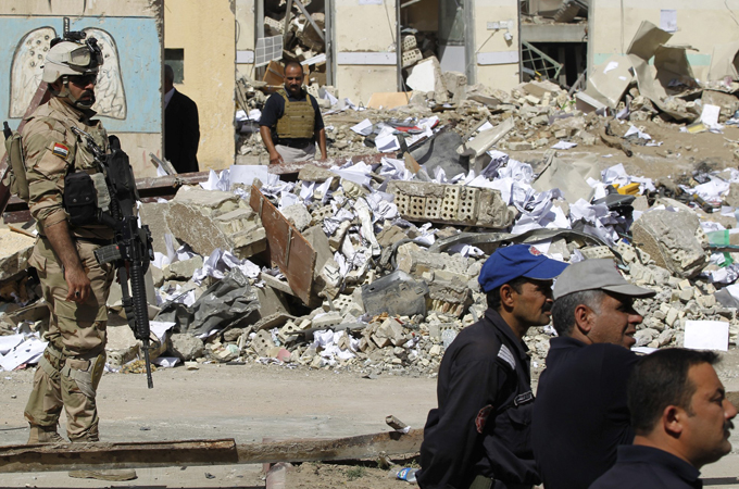 Iraqi security inspect the site of a bomb attack in Baghdad.  (Photo Courtesy of Al-Jazeera)