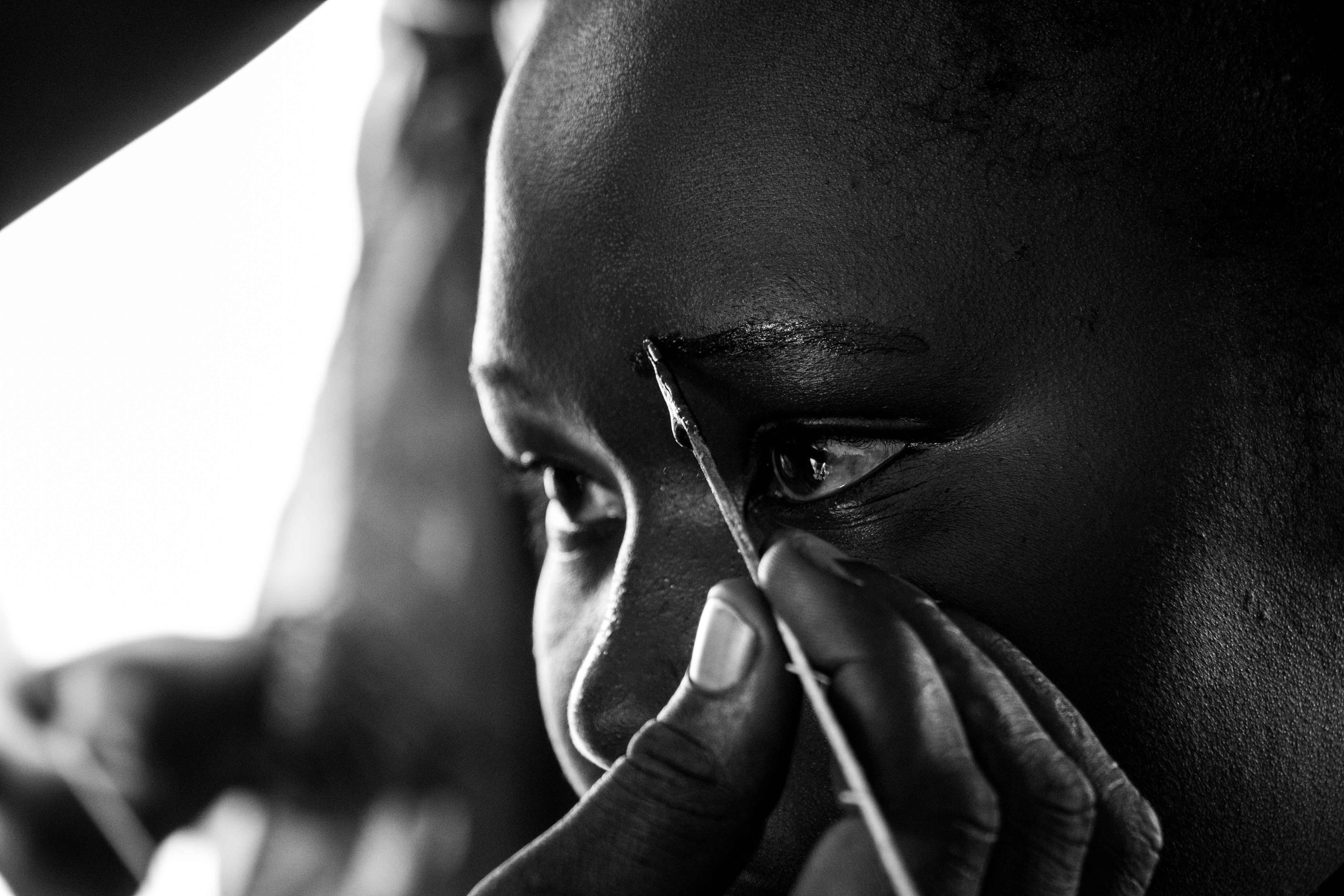 A young Shilluk woman has her eyebrows dyed with black henna in a tent designated a 'women-friendly space' inside Malakal PoC camp. Women in the camp have few opportunities to escape the grim conditions, and they come to this space to relax, socialise and exchange information. [Ashley Hamer/Al Jazeera]