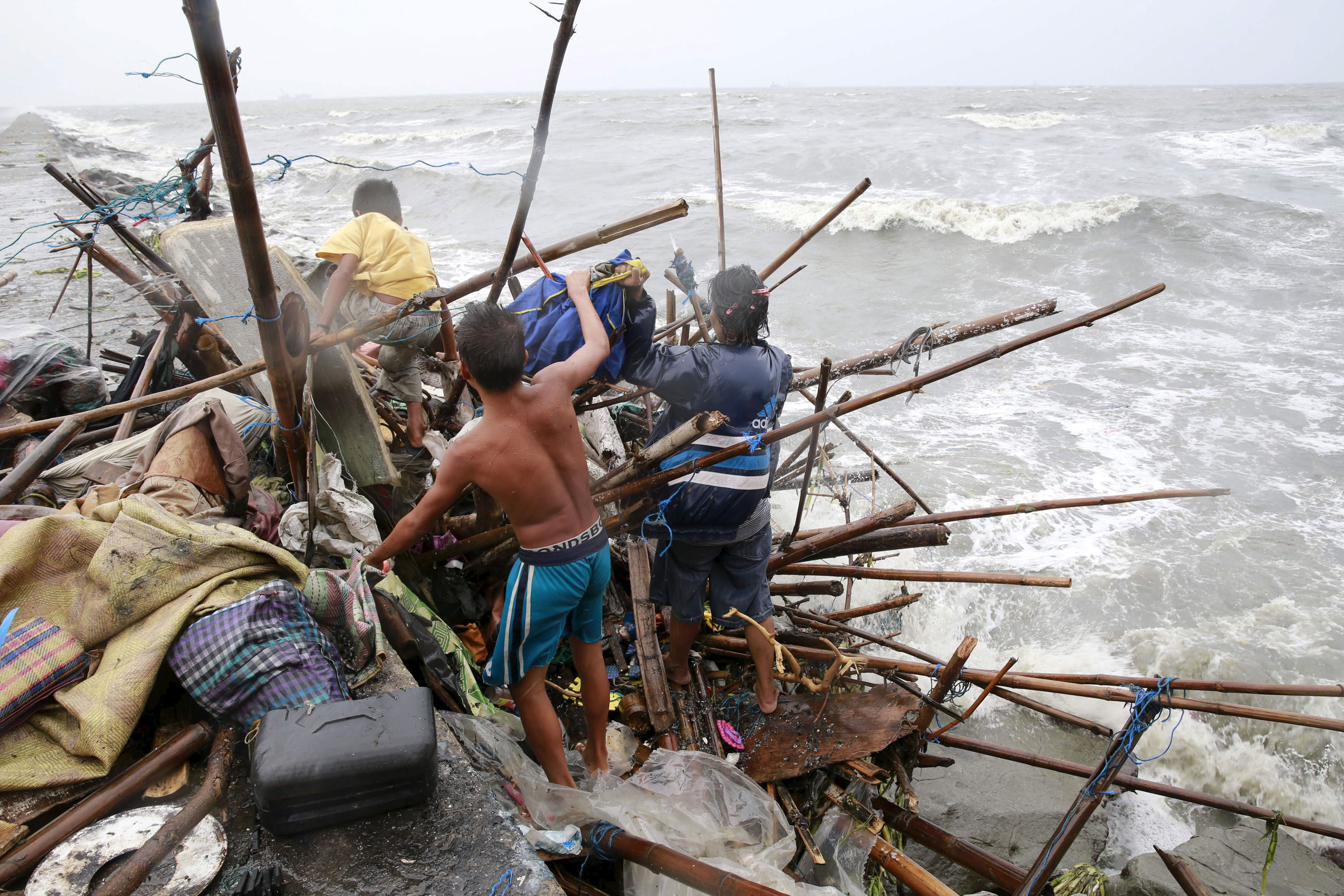 A Taroyo family living along the coast of Manila Bay searches for salvageable items after their house was damaged by strong winds. [Romeo Ranoco/Reuters]