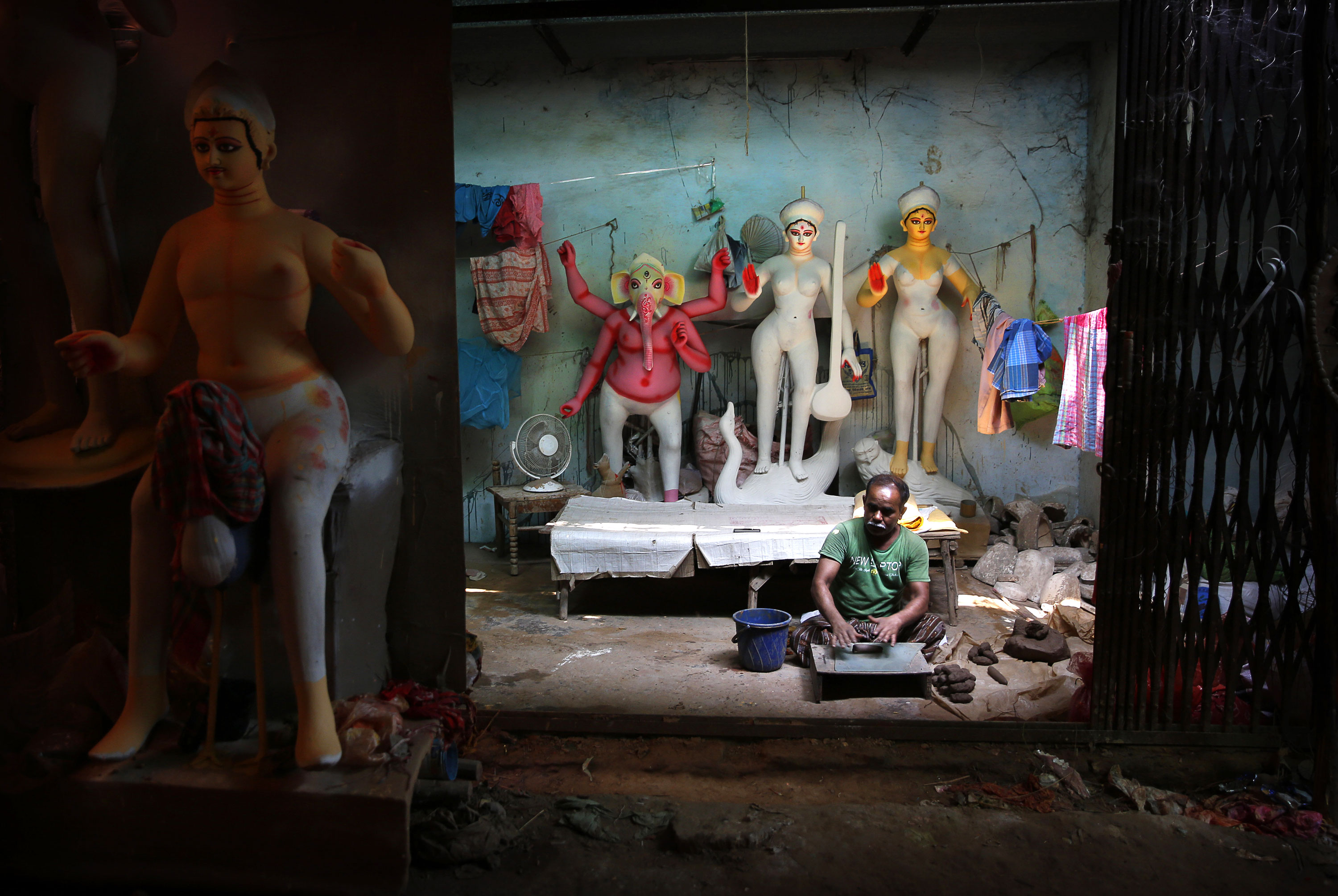 An artist moulds clay as he works on an idol of Hindu Goddess Durga in preparation for the Durga Puja festival. [Manish Swarup/AP]