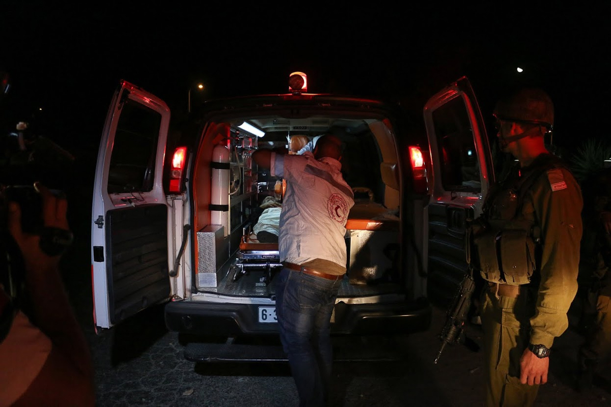 A Palestinian medic loads an injured protester into the ambulance as an Israeli soldier watches on outside the Beit El settlement near Ramallah. [Muhannad Darabee/Al Jazeera]