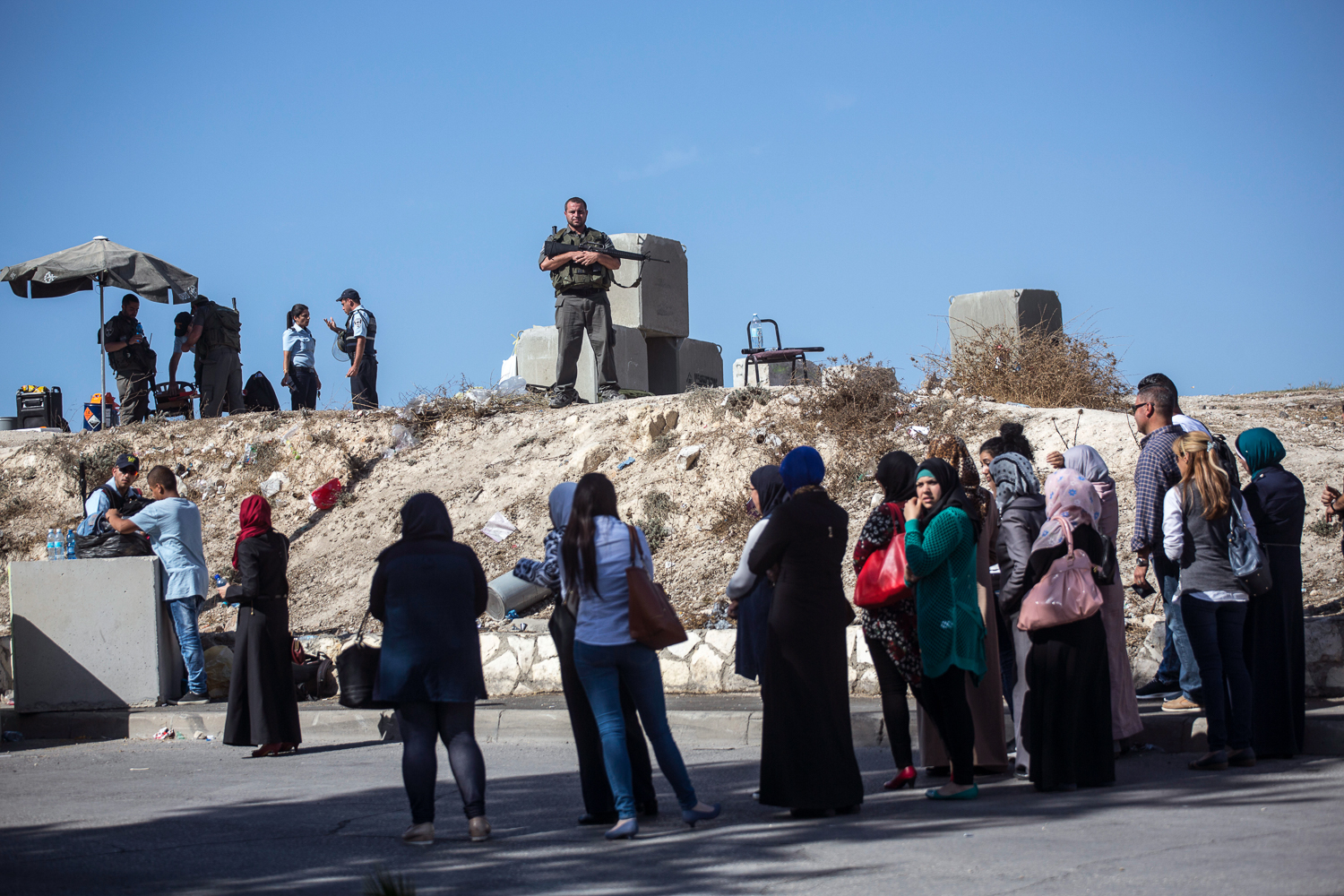 Palestinians wait in line at one of the new checkpoints in al-Issawiya. Several checkpoints have been put in place around the village, making it difficult for residents to move around freely. [Anne Paq/Al Jazeera]