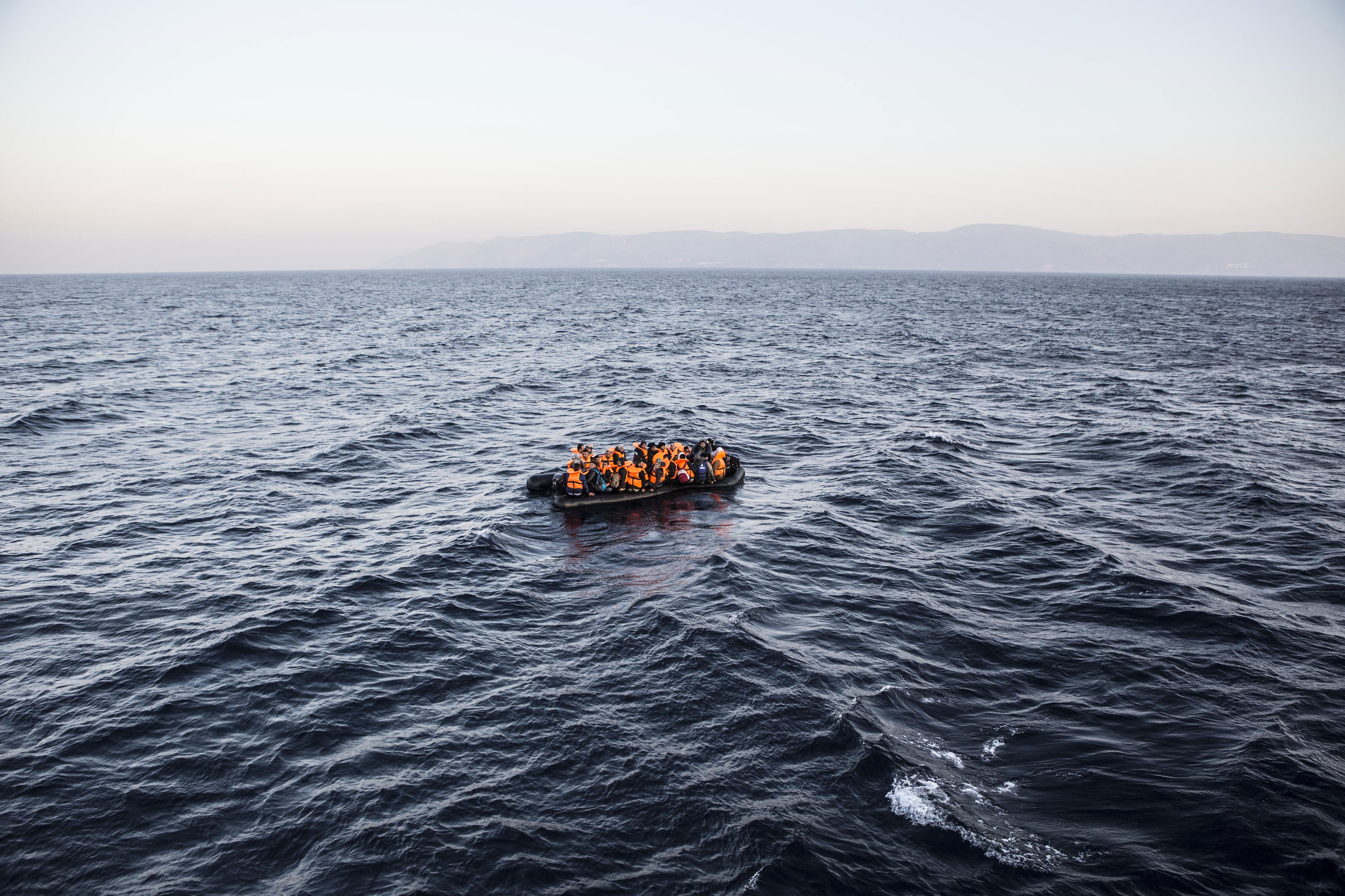 An inflatable boat full of refugees sails off the Greek island of Lesbos after leaving Turkish waters. [Anna Pantelia/Al Jazeera]