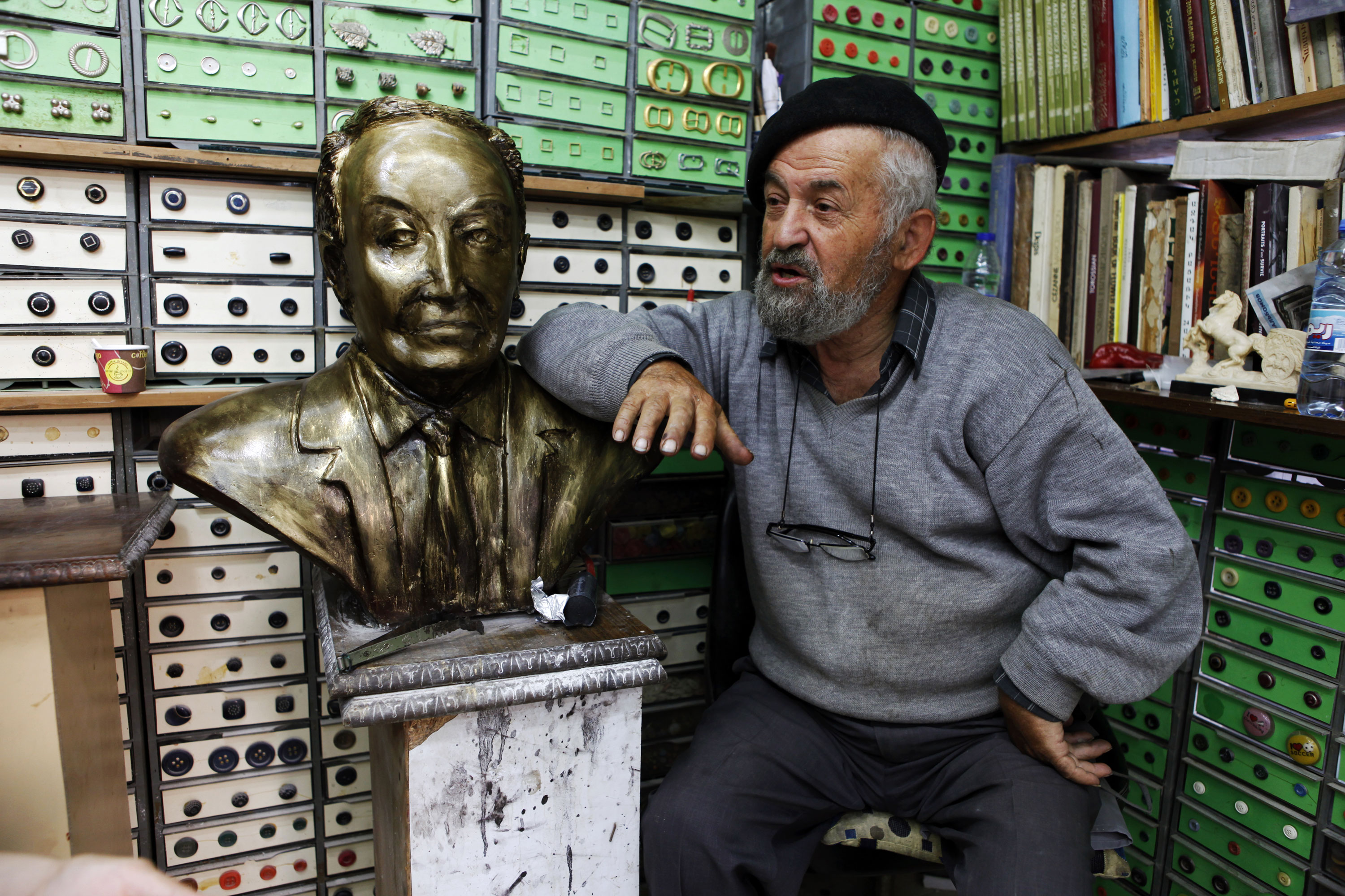 Sculptor, button-maker and local neighbourhood personality Ashod Tazian tells his life story in his shop on one of Bourj Hammoud's main shopping streets. [Adrian Hartrick/Al Jazeera]