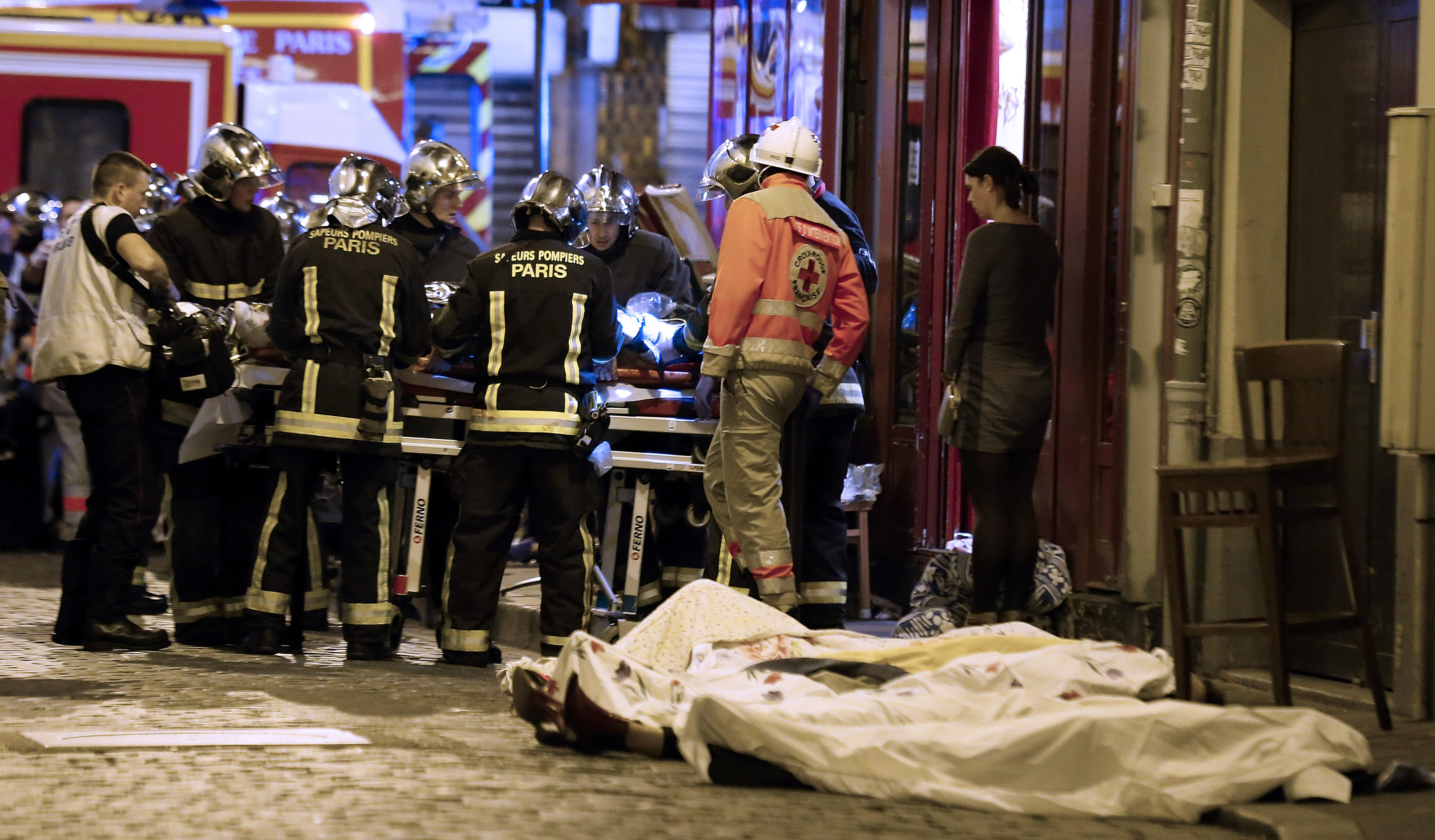 Rescue workers and victims in the 10th district of Paris. At least 120 people were killed in a series of attacks around Paris on Friday. [Jacques Brinon/AP Photo]