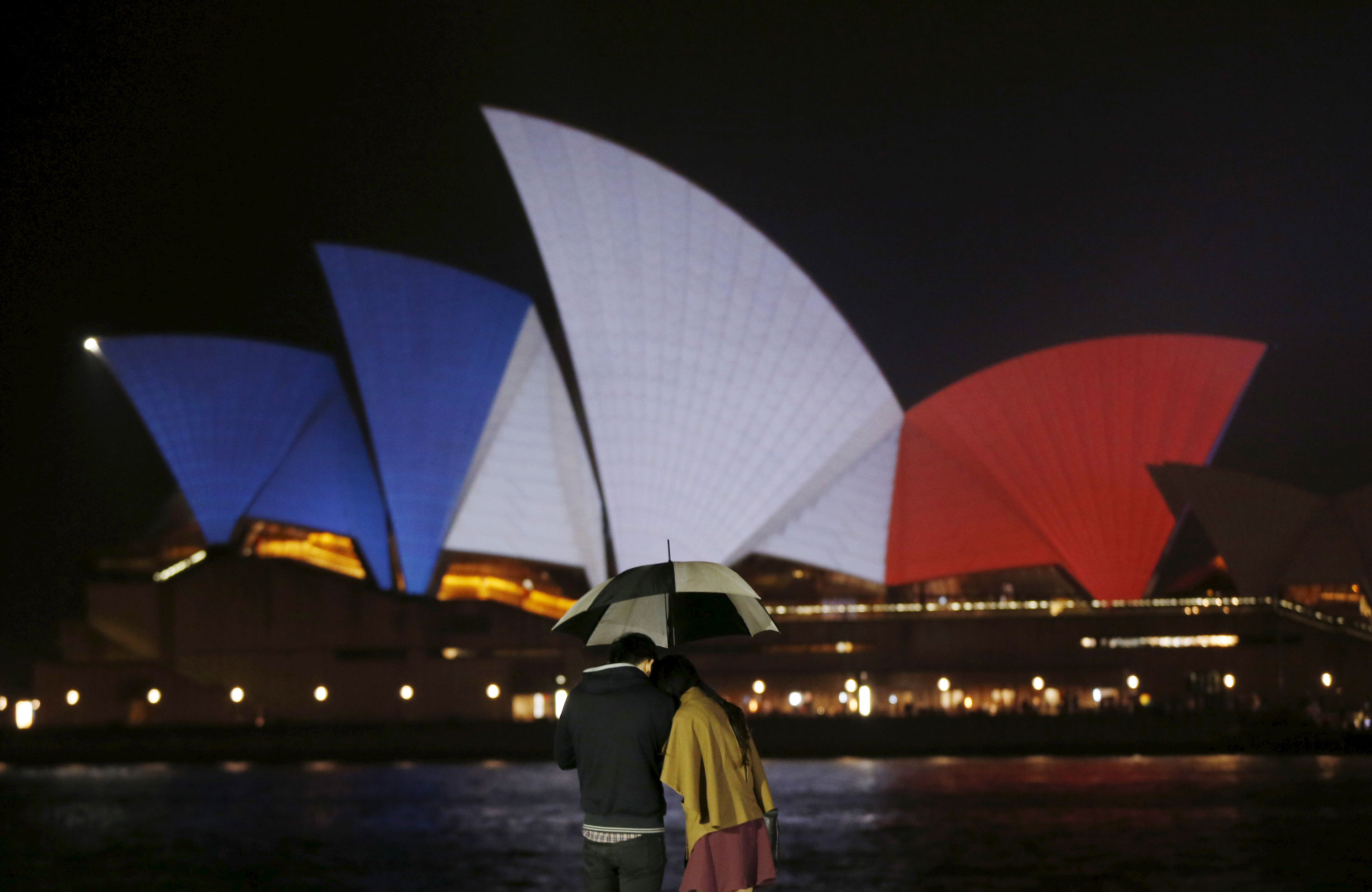 A couple stands in the rain as the blue, white and red colours of France's national flag are projected onto the sails of Sydney's Opera House in Australia. [Jason Reed/Reuters]