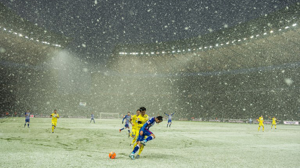 Two football players clash as German teams play in the snow at the Olympic Stadium in Berlin [AFP]