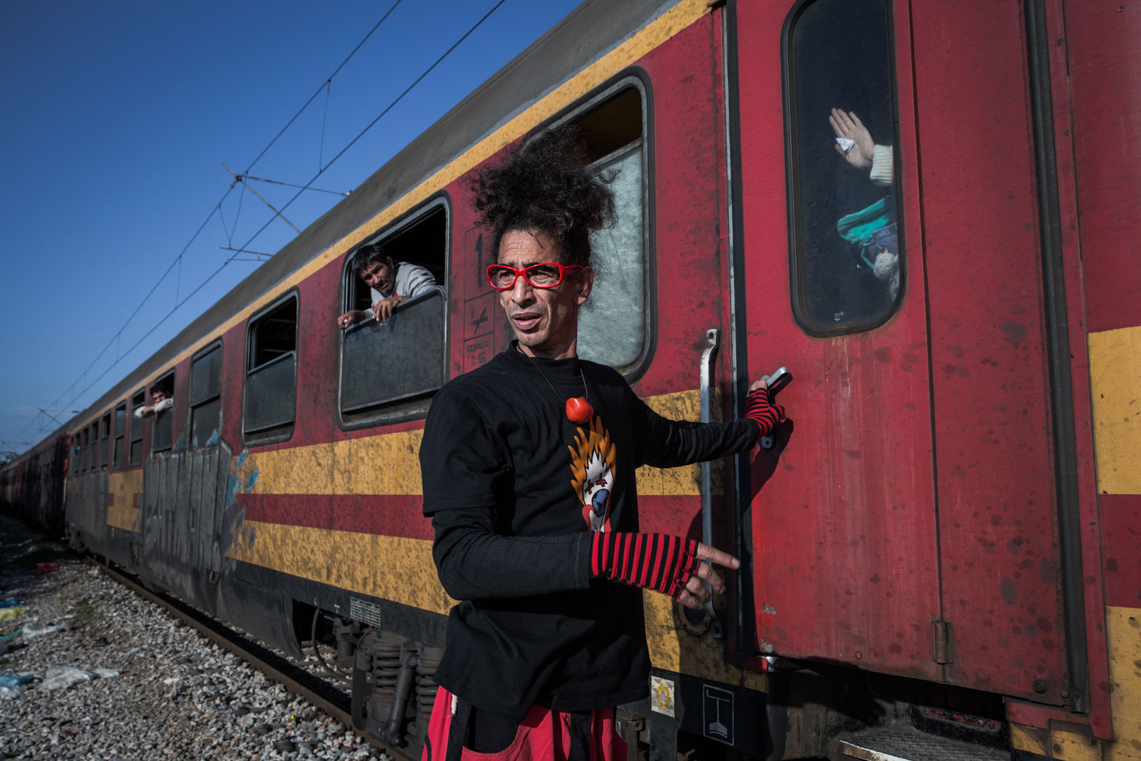 Marcelo XY from Clowns Without Borders tries to help a refugee woman get out of the train in the transit camp in Gevgelija, Macedonia. Travelling with an infant, she was banging on the window, saying her baby didn't have enough air to breathe. [Ioana Moldovan/Al Jazeera]