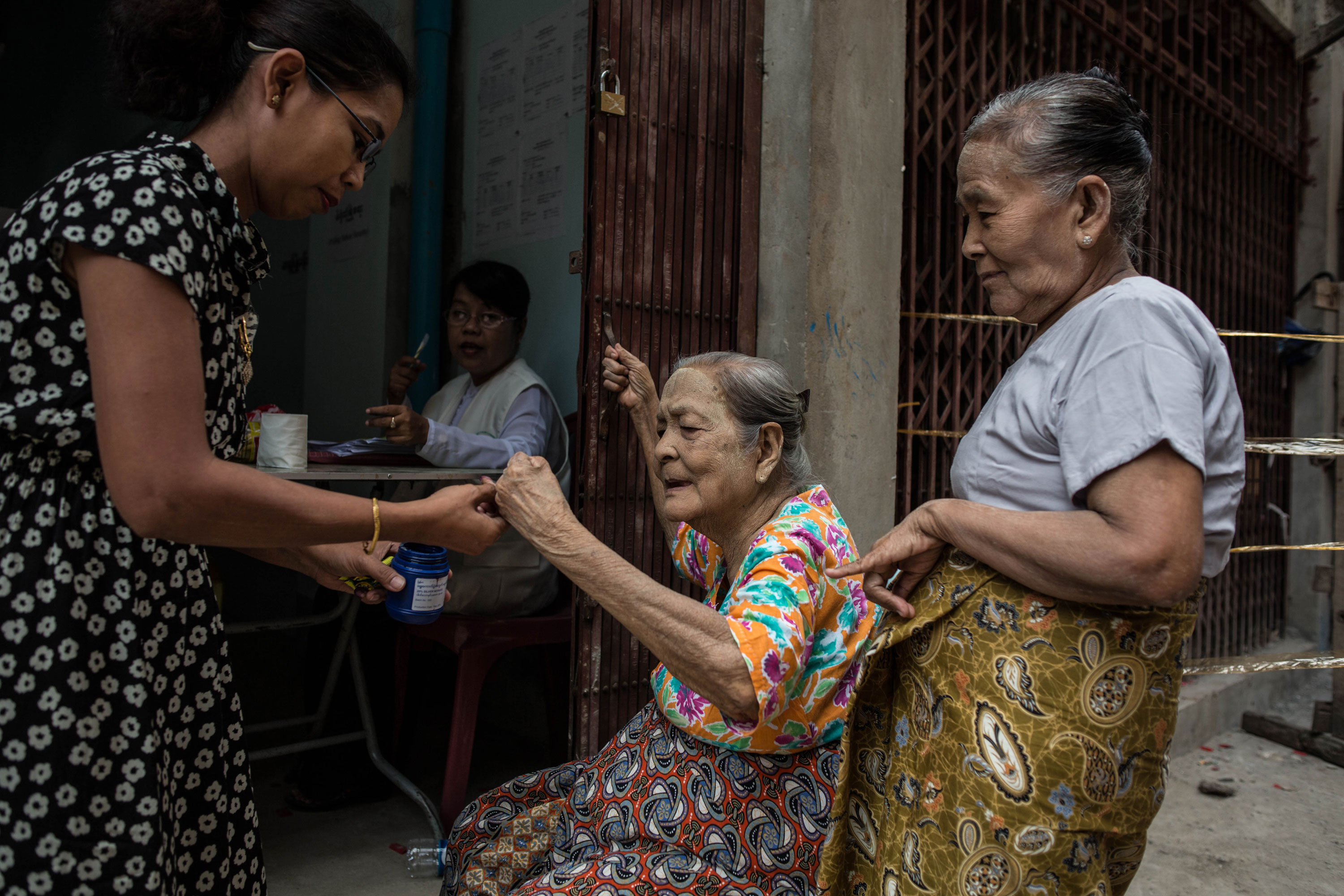 An eldery woman has her smallest finger dipped in purple ink indicating that she has cast her vote. [Andre Malerba/Al Jazeera]