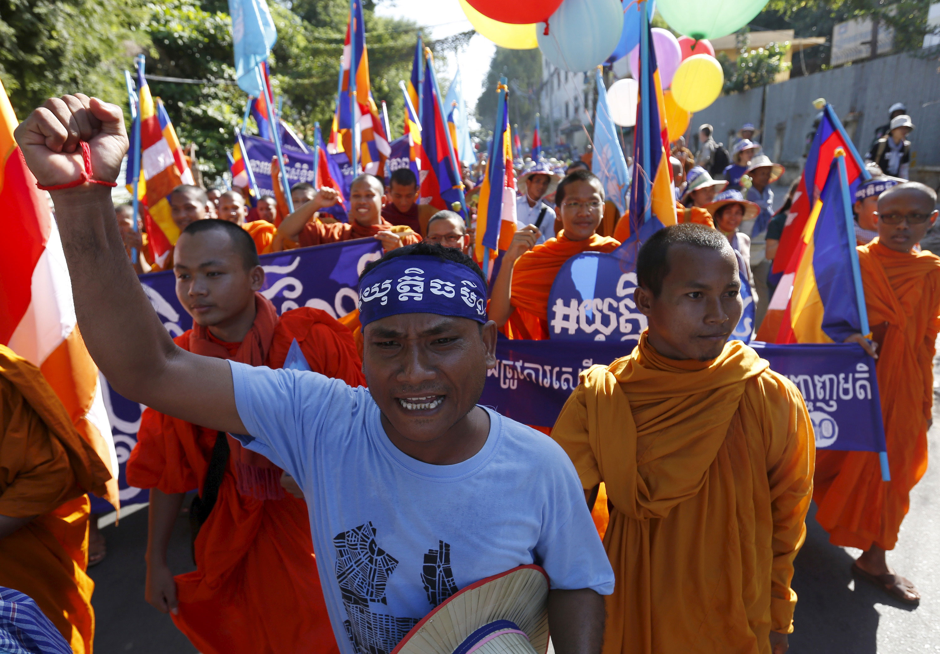 Buddhist monks walk along a street during a march to celebrate Human Rights Day, in Phnom Penh, Cambodia. [Samrang Pring/Reuters]