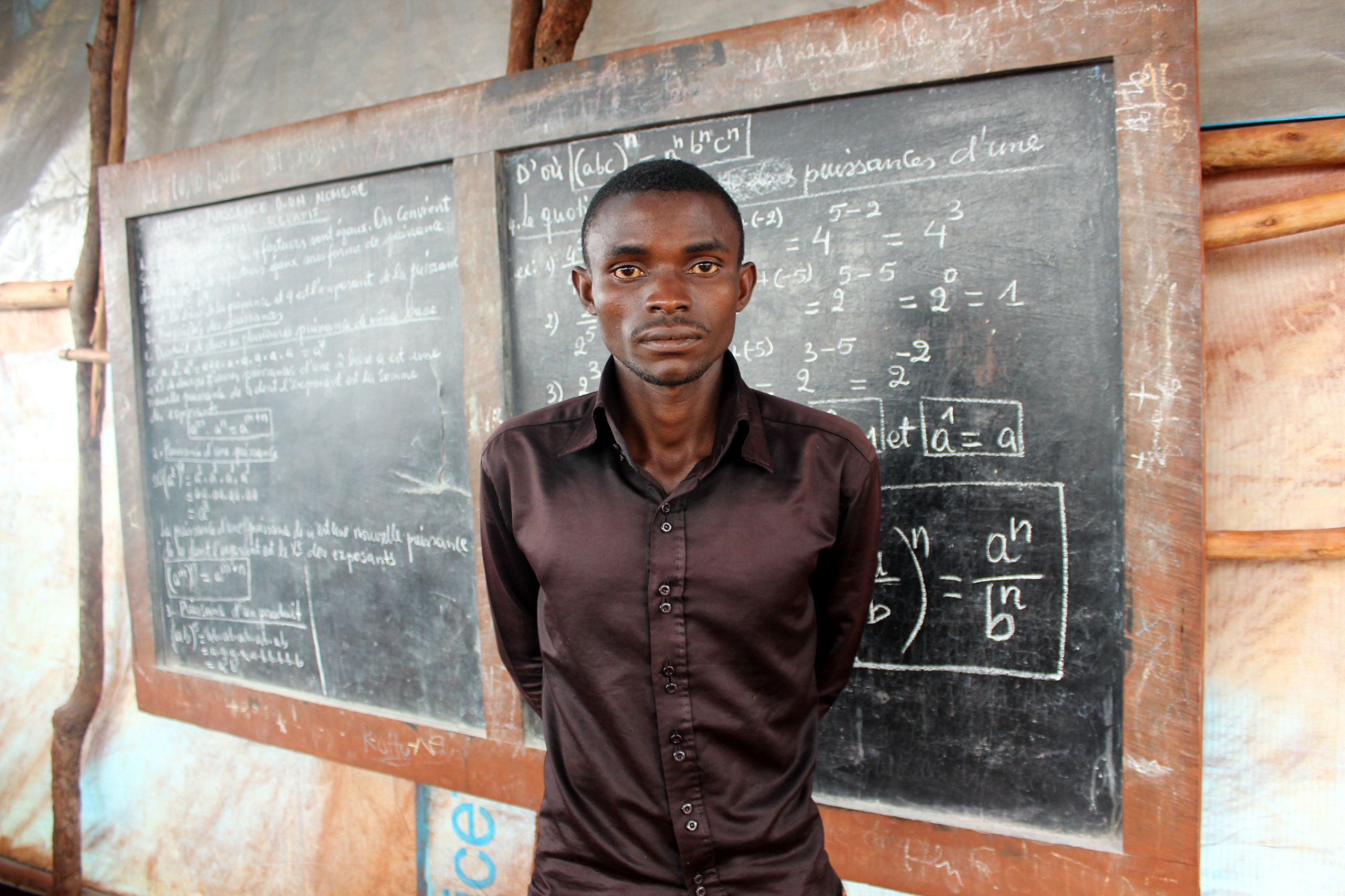 John Posco, 27, was a second-year university student when he was forced to flee from Burundi. He now teaches English and art to high school students in Nyarugusu camp in Tanzania. He hopes an international effort will help resolve the crisis in Burundi. [Tendai Marima/Al Jazeera]