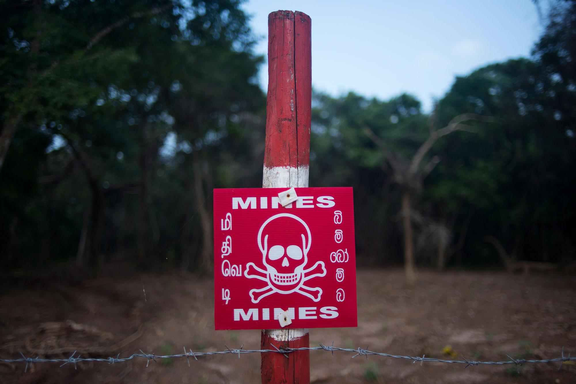 A sign warns of hidden landmines in Mullivaikal on the northeastern coast of Sri Lanka. [Miguel Candela/Al Jazeera]