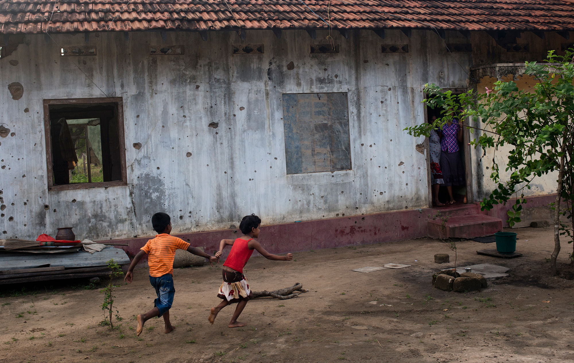 Children play outside their bullet-riddled home in Mullivaikal, which is where the final battle of Sri Lanka's civil war took place. [Miguel Candela/Al Jazeera]