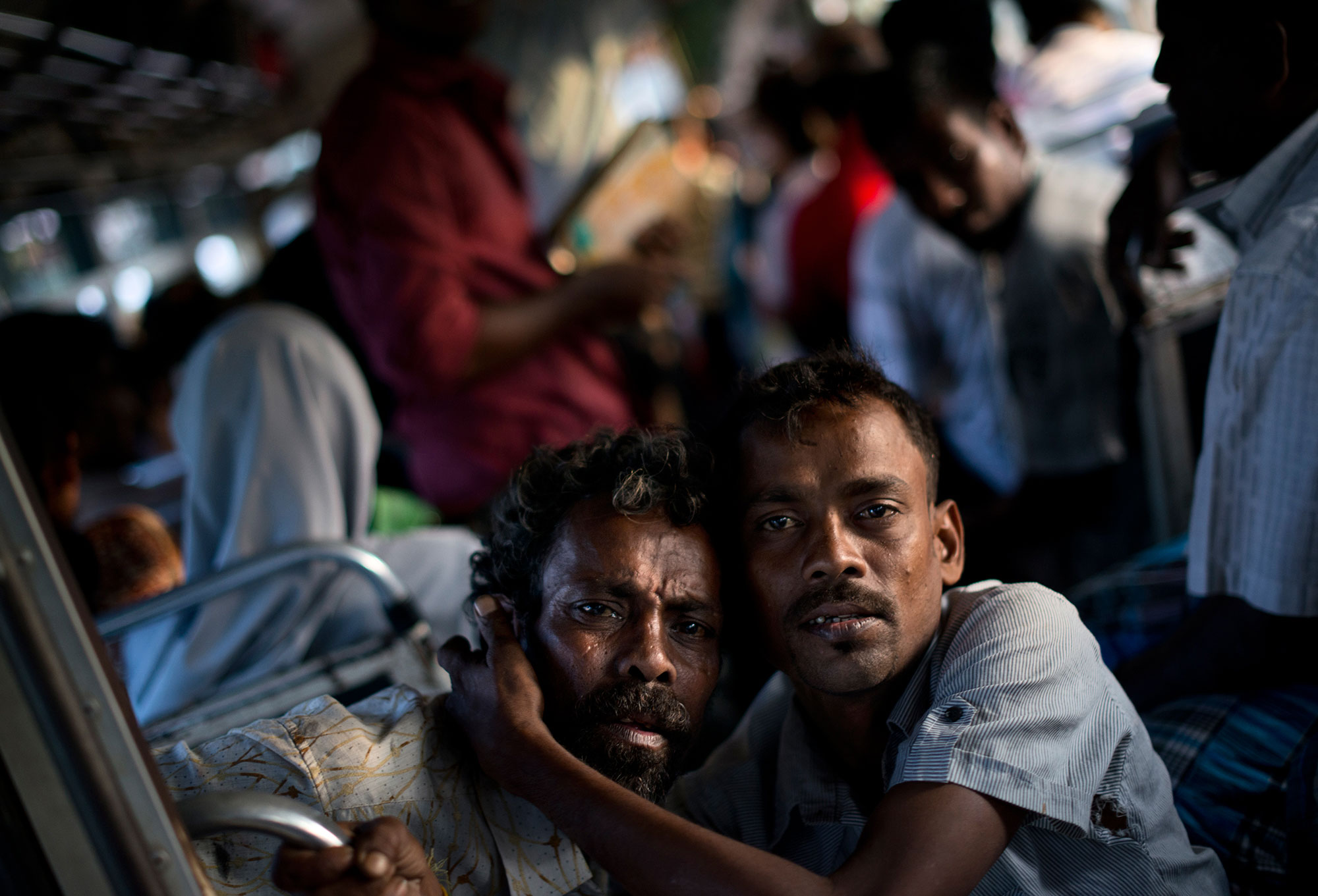 Two intoxicated Tamil passengers ride on a battered local bus. [Miguel Candela/Al Jazeera]