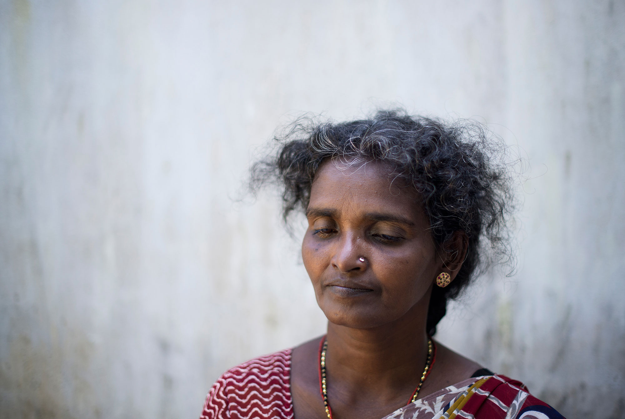 'In the last weeks of the war, my family had been dispersed, but on May 14, 2009, we all managed to get together in the 'safe zone' the army had established in Mullivaikal. They said civilians wouldn't be harmed there, so we found shelter in a small house ... We were happy to be together at last. But that same night, the building was shelled ... My husband was lying on the ground and, when I turned him around, I saw his chest open. He was dead. Next to him was my oldest daughter. She was holding her intestines in her hands, sure that she was going to die,' remembers Balasubramaniam Annaludchumy, who lost five members of her family that night. [Miguel Candela/Al Jazeera]