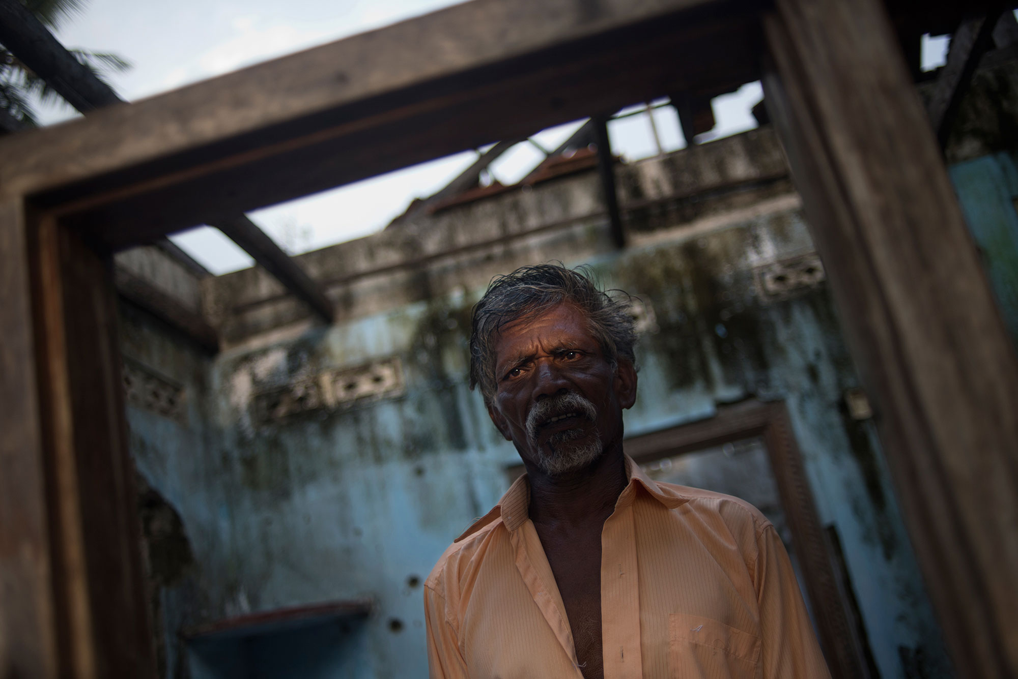 Anthony Fernando, a Tamil civilian, stands at the entrance of his house in the Mullaitivu district, which was badly damaged during the fighting. His wife and daughter were killed during the war. [Miguel Candela/Al Jazeera]