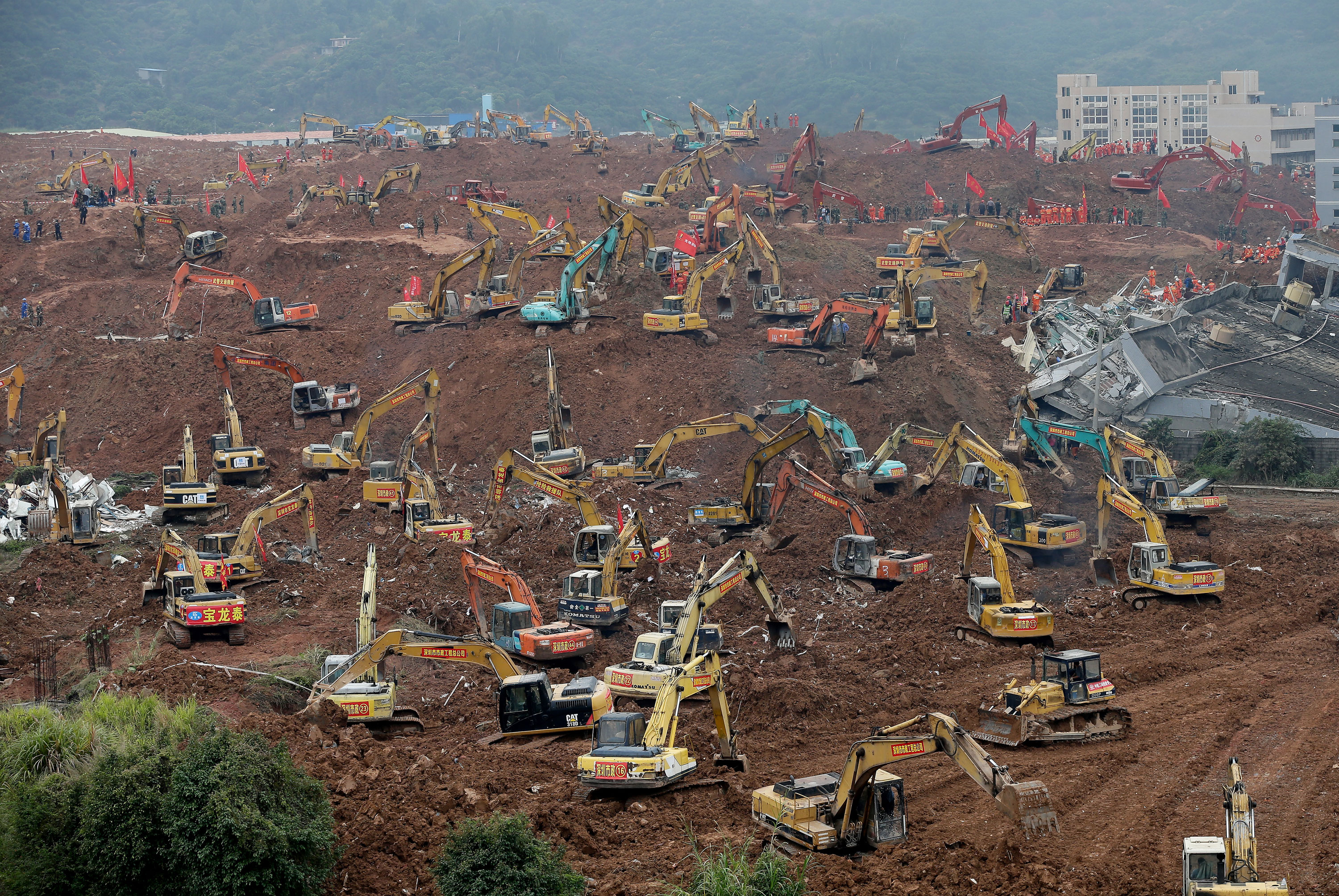 Rescuers use excavators dig the sea of soil to search for potential survivors following a landslide burying buildings at an industrial park in Shenzhen, in south China's Guangdong province [Andy Wong/AP]
