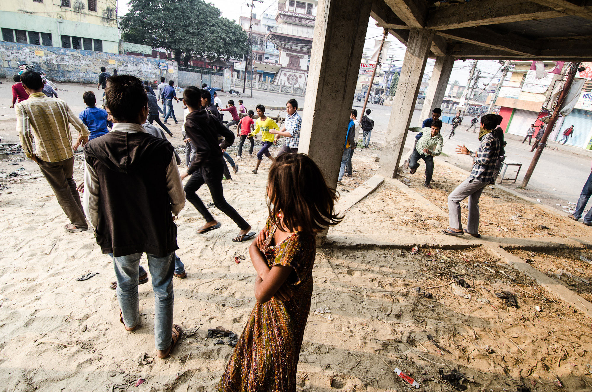 Stone-throwing protesters run away from the Nepali police during clashes in the center of Birgunj.  [Valerie Plesch/ Al Jazeera]