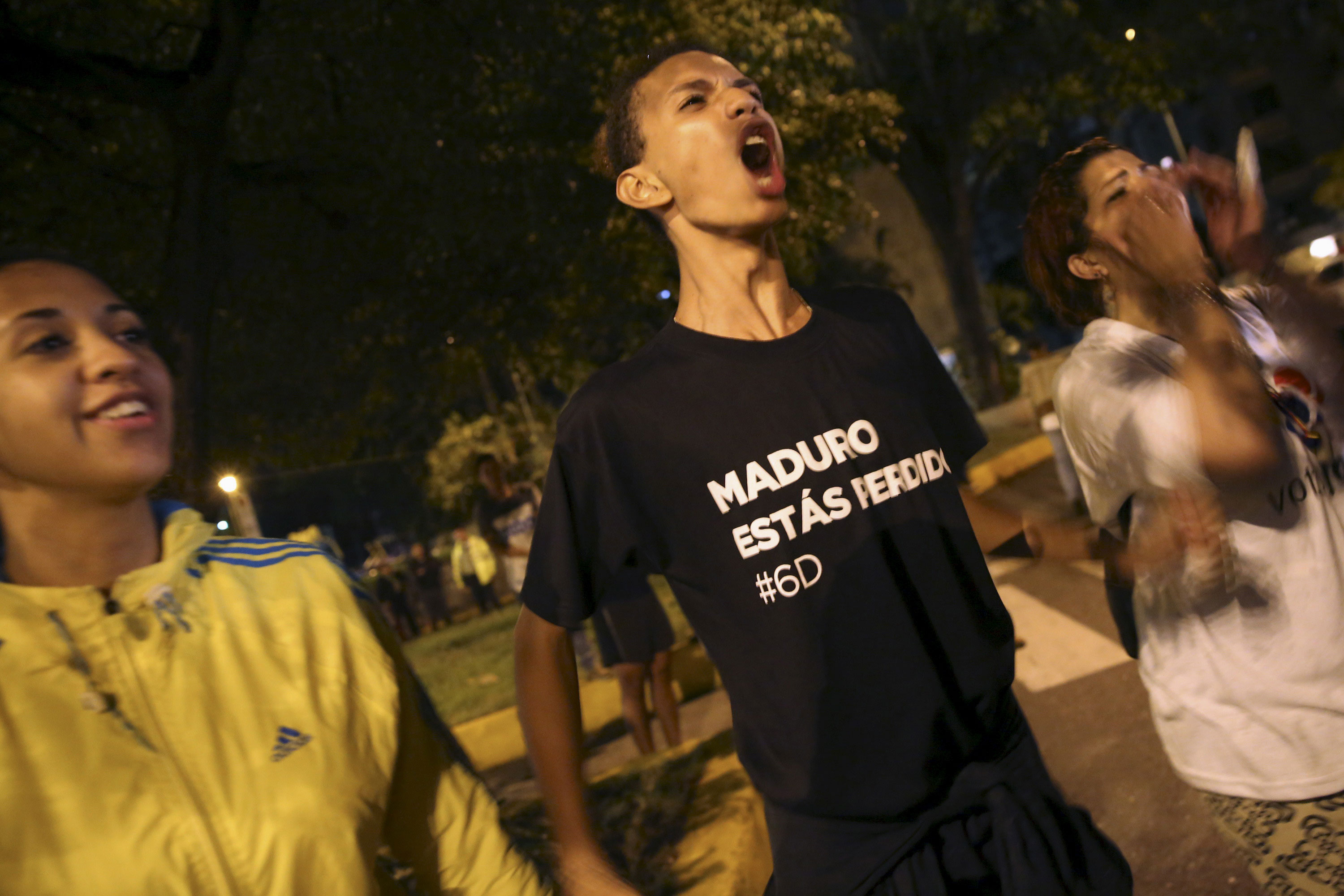 An opposition supporter wearing a T-shirt that reads 'Maduro, you are lost' shouts while he celebrates their victory on a street in Caracas. [Nacho Doce/Reuters]