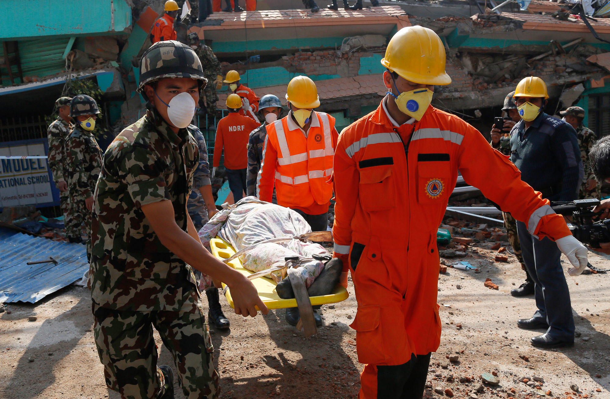 Rescue teams carry a body dug out of the collapsed Sitapyla church in Kathmandu. [AP Photo/Wally Santana]
