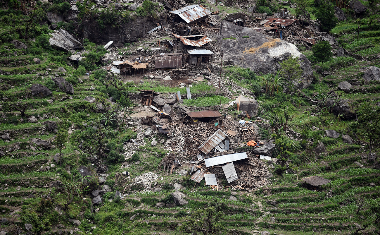 Damaged houses are seen from an Indian army helicopter in the Nepalese area of Gorkha. Hungry and desperate Nepalese villagers rushed towards the helicopter begging to be airlifted to safety. [AFP PHOTO/Sajjad Hussain]
