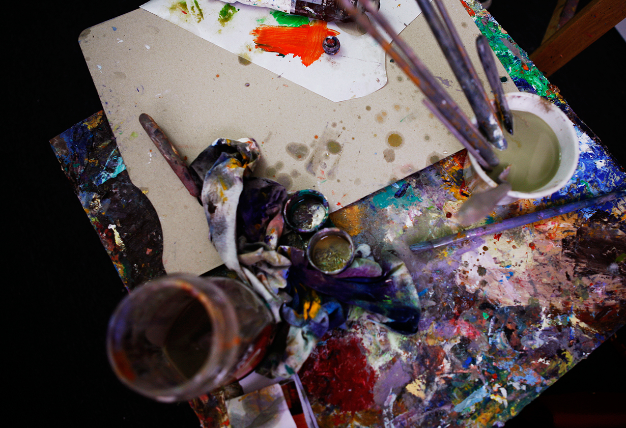 Brushes and paints are laid out in Jordanian artist Ghassan Abu Laban's studio in Amman. [Silvia Boarini/Al Jazeera]