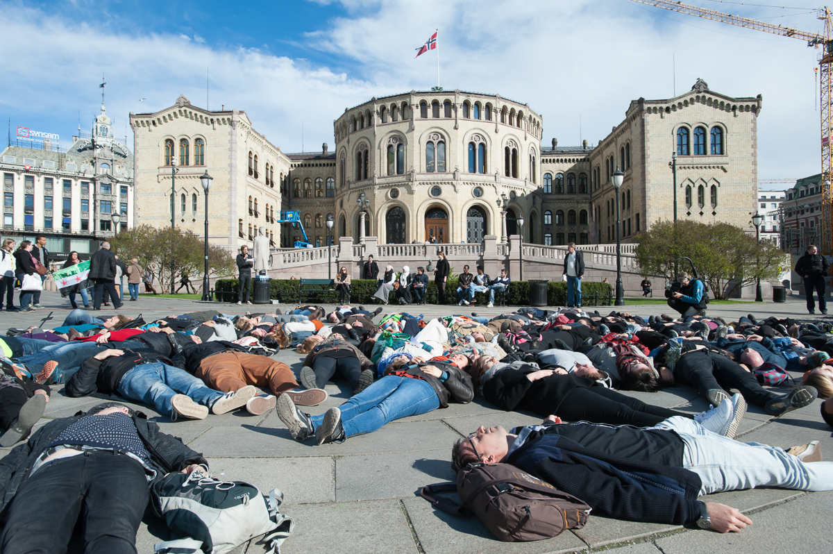 Oslo activists staged a 'die-in' protest in front of Norway's parliament building to demand greater action to aid refugees crossing the Mediterranean Sea. [Ryan Rodrick Beiler/Al Jazeera]