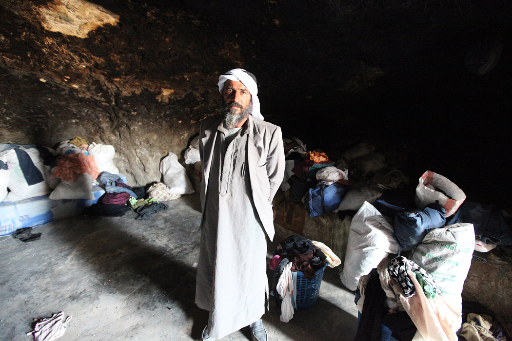 Mahmoud Hussein Hamamdi stands in his cave in the hamlet of Um Faqarah. 'In 2007, I decided to build a brick house because I could not live with my two wives and 14 children in that one cave,' he said. 'But on November 24, 2011, Israeli bulldozers destroyed the house, as well as the mosque and the container for the collective power generator.' [Eloise Bollack/Al Jazeera]