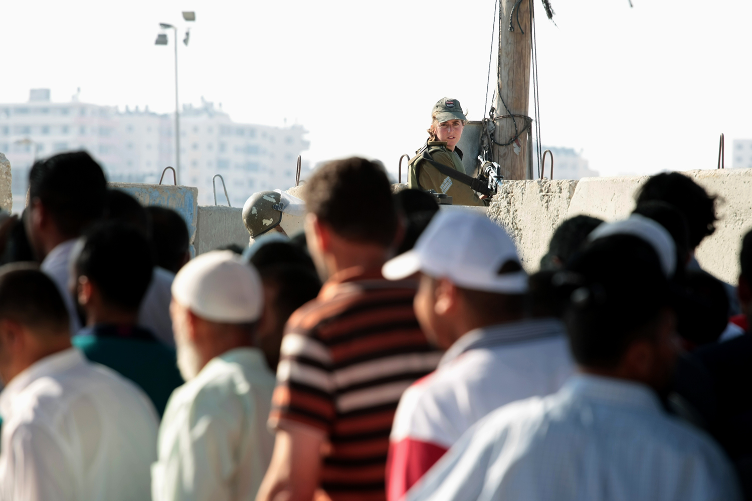 "An Israeli soldier monitors Palestinians' entry through the Qalandiya checkpoint to pray at Al-Aqsa mosque in Jerusalem during the holy night of Laylat al-Qadr. Known as the ""Night of Power,"" it falls on an odd-numbered night during the last 10 days of Ramadan. [Mohammad Alhaj/Al Jazeera]"