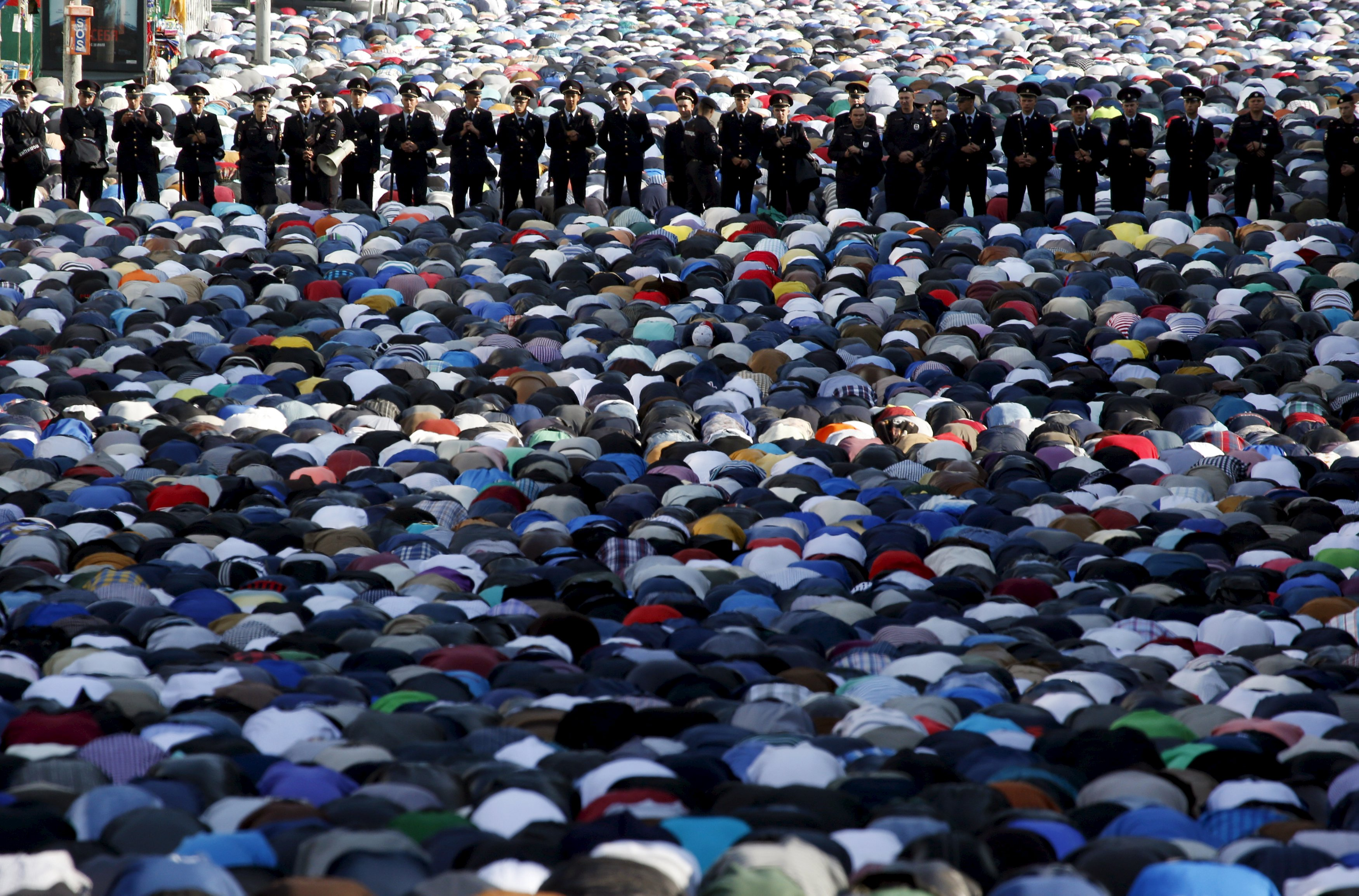 Police stand guard as Muslims attend the