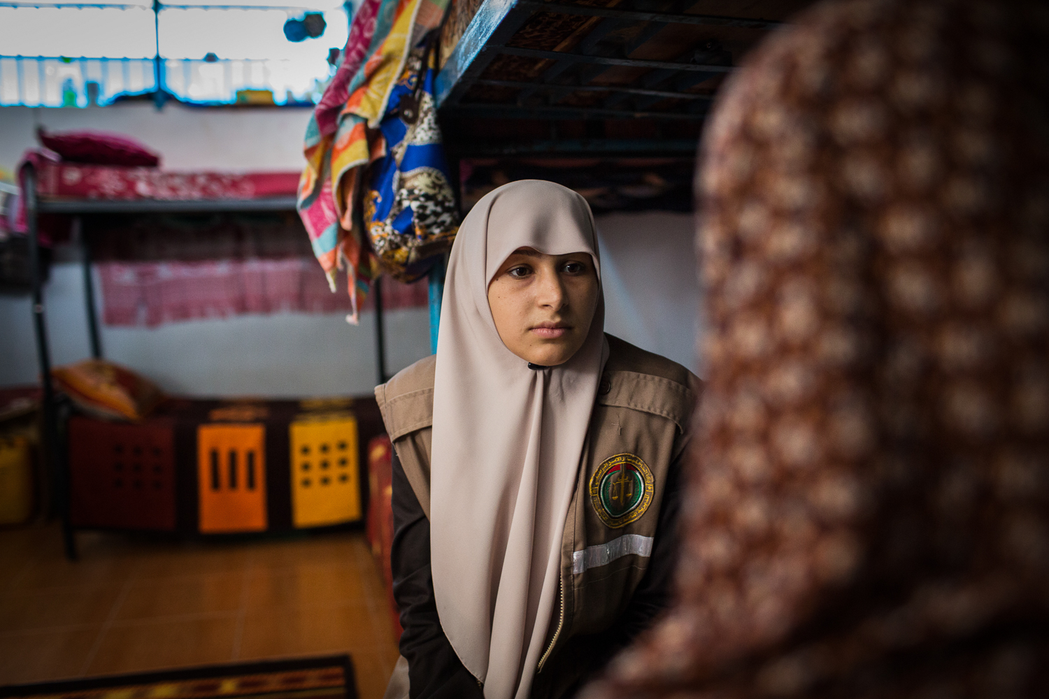 Umm Ahmed, who works as both a prison supervisor and social worker, talks to a prisoner at Gaza's Reform and Rehabilitation Centre for Women. [Celia Peterson/Al Jazeera]