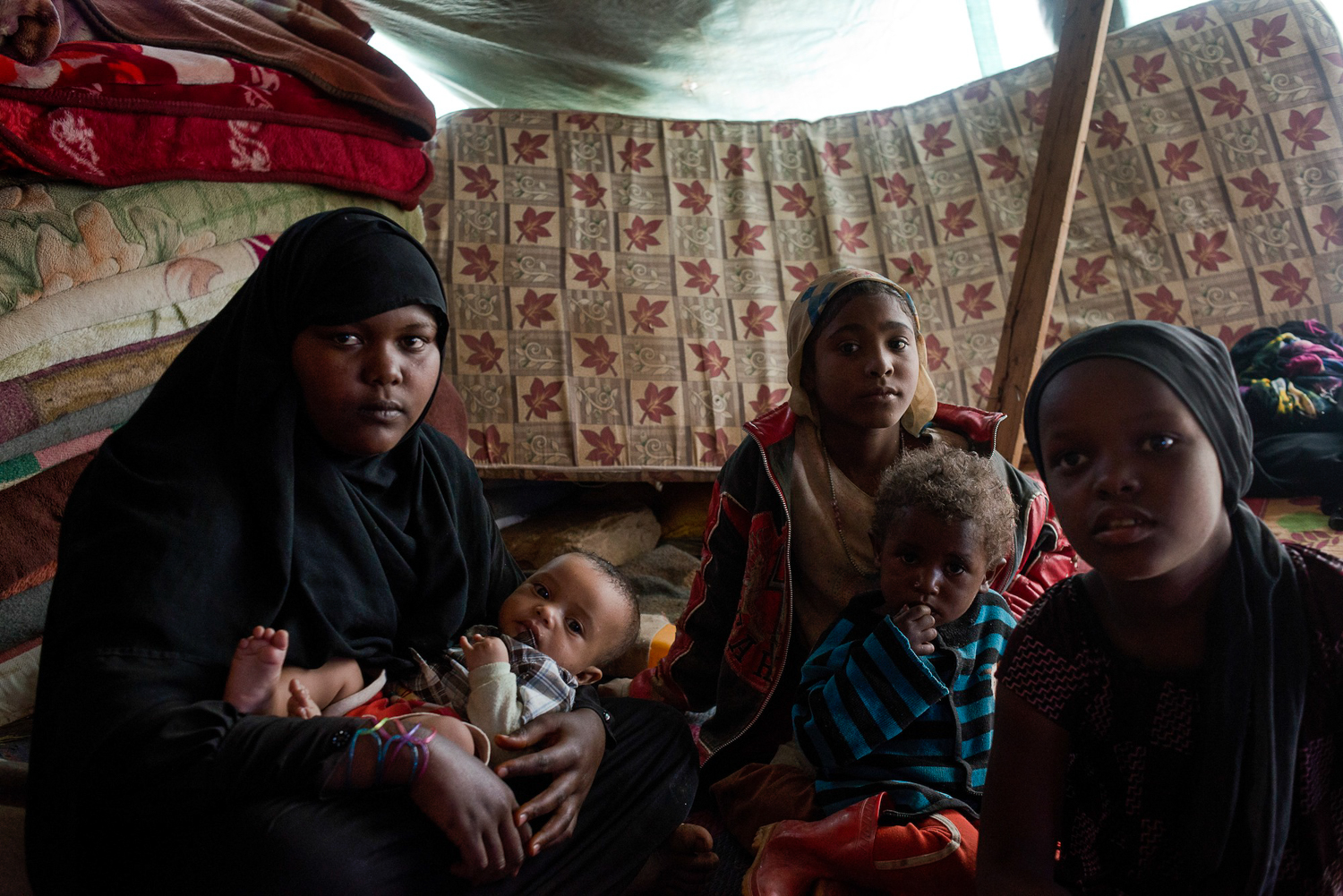 A Yemeni family from the Muhamashin community sit in their makeshift tent in an unofficial, displaced persons camp in Khamer, Yemen. [Alex Potter/Al Jazeera]