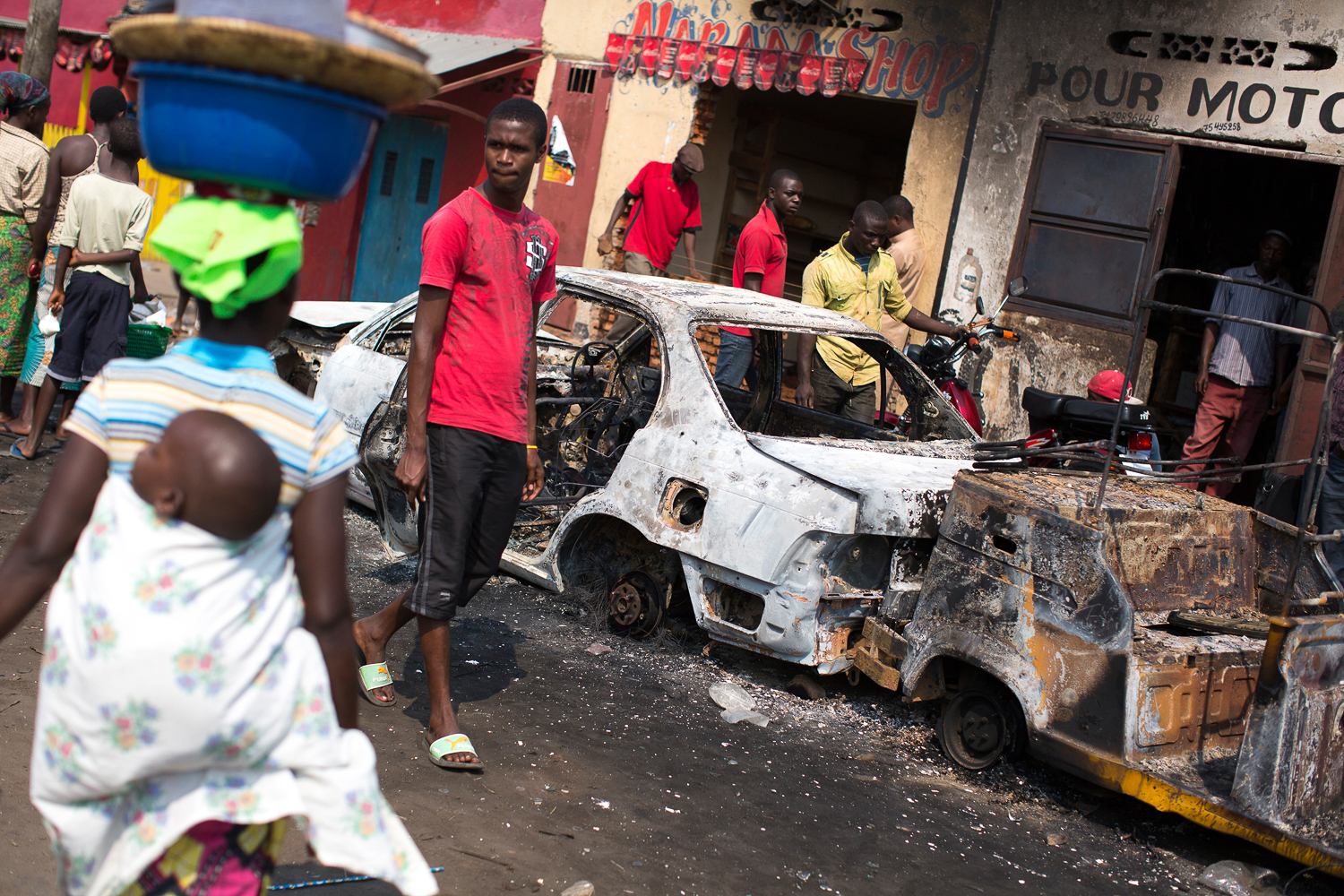 Local residents walk past a burned-out car and tuk-tuk in Cibitoke, Bujumbura, on the morning of August 4th. [Griff Tapper/Al Jazeera]