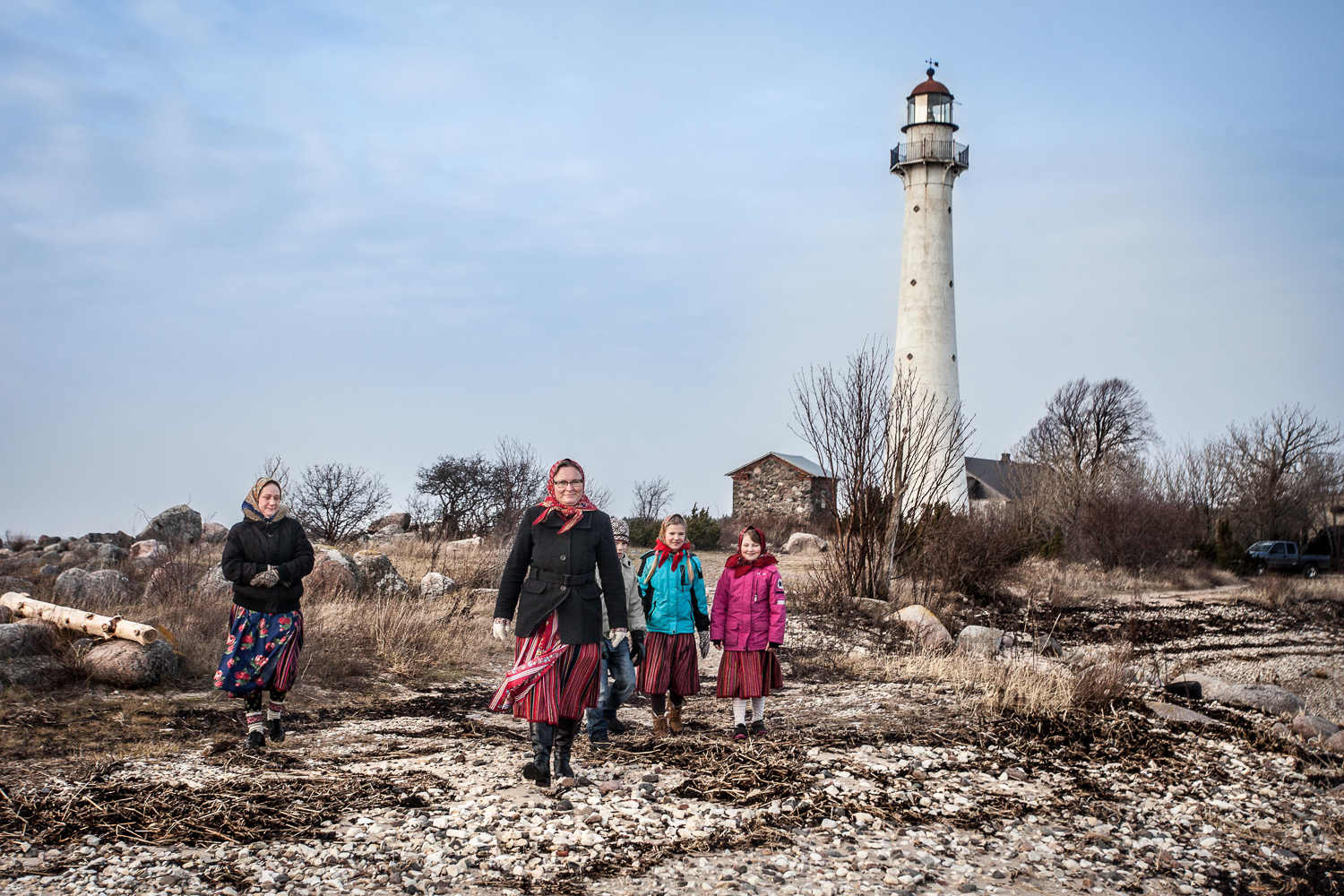 Mare Matas, leader of the island and president of the Kihnu Cultural Space Foundation, walks past a 19th century lighthouse. [Sebastien Leban/Al Jazeera]