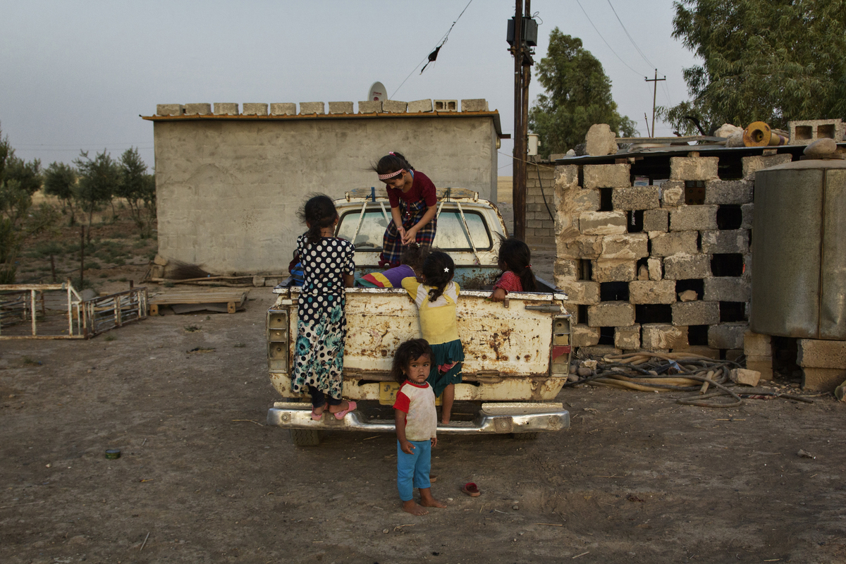 A group of displaced children play on the back of a pickup truck at a chicken farm in Dibaga. About 260 residents of the Iraqi village of Jarallah have relocated here, driven out of their homes by the ongoing conflict. [Hawre Khalid/Metrography/Al Jazeera]