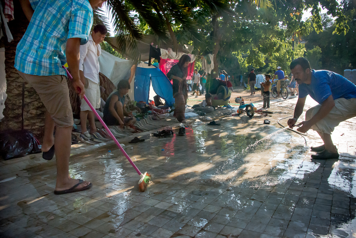 Refugees and volunteers clean the pathways of the camp. [Dimitris Sideridis/Al Jazeera]